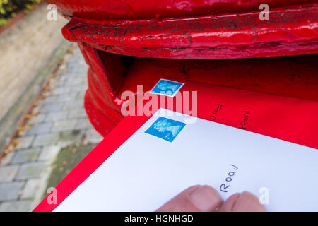 Posting a letter in a red british post box. - Stock Image