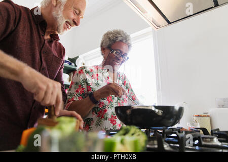 Active senior couple cooking in kitchen - Stock Image