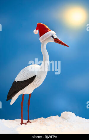 White Stork with Christmas Hat in Snow - Stock Image