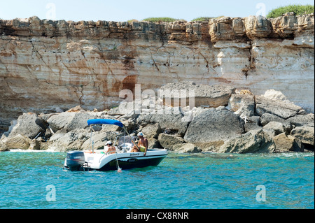 Pleasure boat at anchor under limestone cliffs, Crete Greece - Stock Image