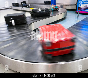 Baggage and suitcases on a luggage carousel at an airport - Stock Image