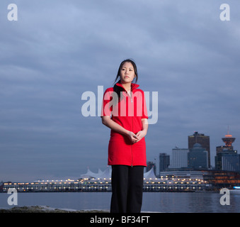 A portrait of a young Asian woman along the Stanley Park seawall with Canada Place beyond, Vancouver, British Columbia, - Stock Image