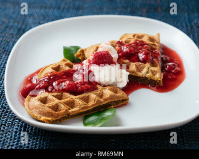 Heart shaped vegan beet waffles with a raspberry sauce. - Stock Image