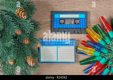 Retro blue audio cassette and christmas decorations on bown wooden background - Stock Image