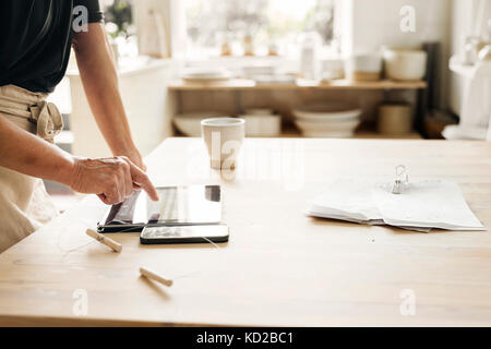 Potter using digital tablet at work - Stock Image