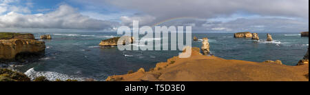 Clearing sky and rainbow over the Bay of Islands along the Great Ocean  Road, Victoria, Australia - Stock Image