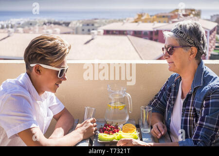 happy leisure activity on the terrace rooftop having breakfast with smiles and happiness for grandmother and teenager family caucasian people. ocean a - Stock Image
