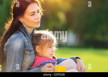 Portrait of mother with daughter relaxing outdoors, spending time together in warm sunny autumn day, loving happy - Stock Image