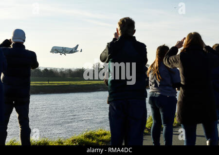 Broughton, Flintshire, UK. 14th February 2019. Crowds watch the new Airbus A330-743L transport plane known as the Airbus Beluga XL land at Hawarden Airport. The airport is adjacent to the Airbus factory on the outskirts of Chester and this is the first visit of the plane to the factory where it will remain until Saturday. The Beluga XL is designed to transport aircraft wings and has 30% more cargo capacity than the current Beluga. Credit: Andrew Paterson/Alamy Live News - Stock Image