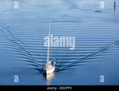 Sailboat driving with motor at inland river , Leppävirta , Finland - Stock Image