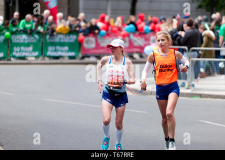 Charlotte Ellis (GBR), with her guide runner, competing in the World Para 2019 London Marathon. Charlotte went on to finish 7th, in a time of 03:23:47in the T11/12 Category - Stock Image