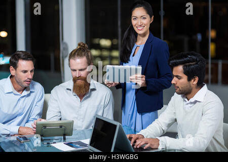 Businesswoman smiling at camera while colleagues discussing over digital tablet and laptop - Stock Image