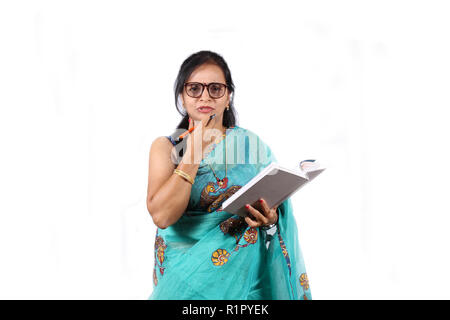 An Indian teacher in Blue Saree asking a question to students, on white studio background. - Stock Image