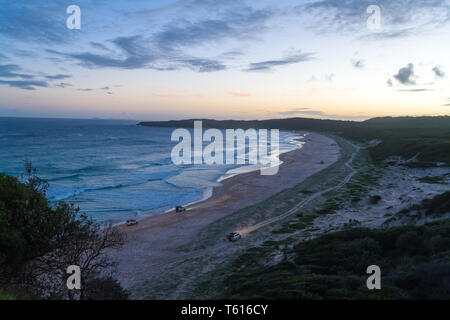 Seal Rocks, NSW, Australia-April 20, 2019: Offroad cars on the beach. View from the lighthouse at Sugarloaf Point Seal Rocks, Myall Lakes National Par - Stock Image
