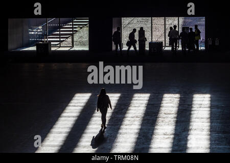 Tate Modern Art Gallery - shadows fall on people walking towards the gallery exit - Stock Image