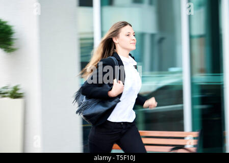 Young businesswoman running on pavement - Stock Image