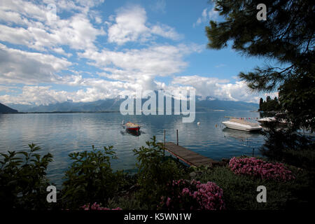 Rowing boats and small yachts moored on a calm and peaceful Lake Geneva in the summer. With the Alp mountains in - Stock Image