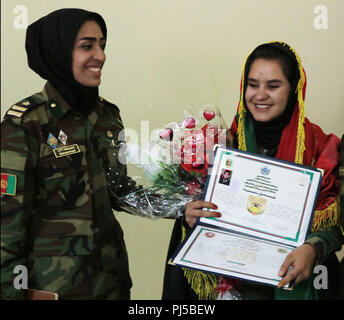 KABUL, Afghanistan (August 29, 2018) -- Sodia (right), an Afghan National Army soldier, poses for a photo after graduating from the Afghan National Army Sergeant Major Academy at Camp Qurgha, Afghanistan, August 29, 2018. She ranked second out of the 80 graduates. (U.S. Army photo by Staff Sgt. Shaiyla Hakeem) - Stock Image