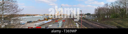The changing skyline of Woking, Surrey: railway tracks lead into tower cranes and new high rise Victoria Square retail development in the town centre - Stock Image