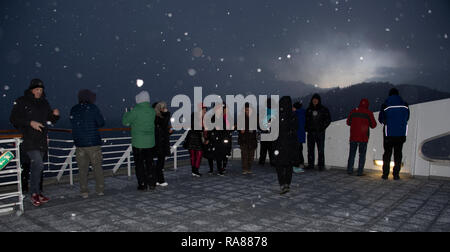 Passengers on board the Hurtigruten coastal steamer, the first time they see snow, Norway. - Stock Image