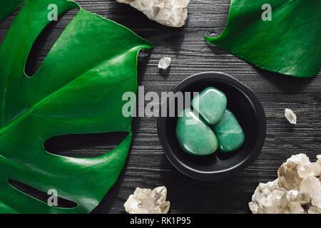 Green Aventurine with Smoky Quartz and Monstera on Black Wood - Stock Image