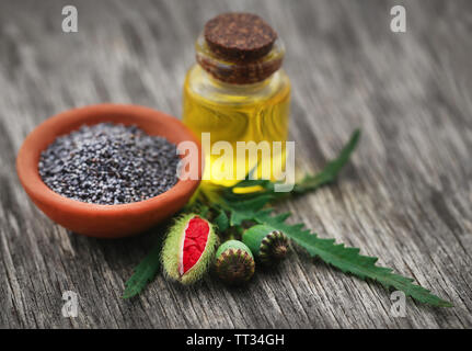 Poppy flower seeds and extract in a bottle on wooden surface - Stock Image