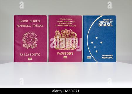 British, Italian and Brazilian passports standing next to each other. - Stock Image