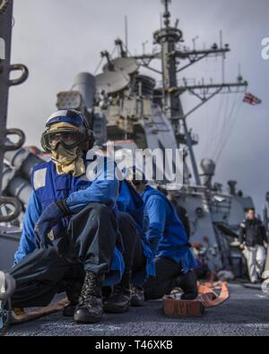 England  (March 12, 2019) Sailors standby on the aft missile deck during a simulated emergency flight quarters drill aboard the Arleigh Burke-class guided-missile destroyer USS Porter (DDG 78) in support of Flag Officer Sea Training in Plymouth, England. Porter, forward-deployed to Rota, Spain, is on its sixth patrol in the U.S. 6th Fleet area of operations in support of U.S. national security interests in Europe and Africa. - Stock Image