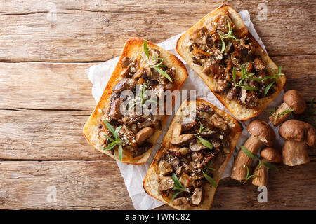 Sandwiches with fried porcini mushrooms, caramelized onions and thyme close-up on the table. Horizontal top view from above - Stock Image