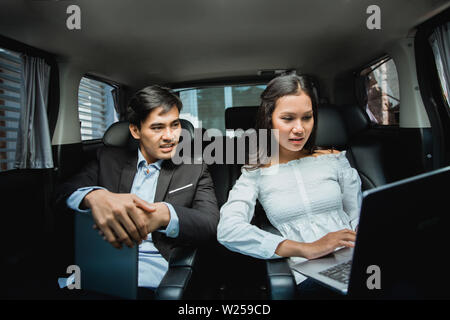 meeting in the car. two asian businessman and woman discussing something while in their way to the office - Stock Image