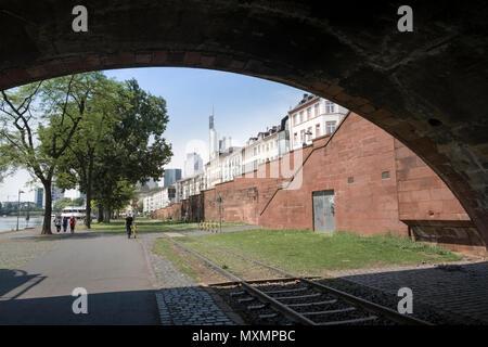 Disused tram tracks underneath a bridge heading towards the city centre, Frankfurt am Main, Hesse, Germany. - Stock Image