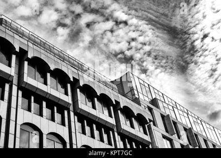 Modern building exterior in an abstract form with dramatic clouds and sky in black and white - Stock Image