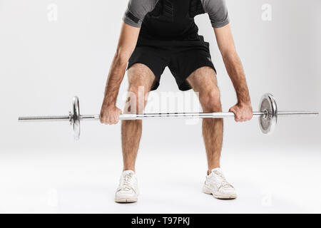 Cropped image of a young sports fitness man isolate over white wall background make exercises with barbell. - Stock Image