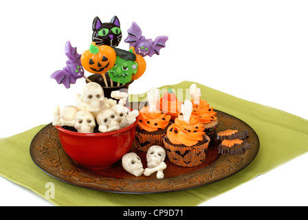 Halloween cupcakes, skeleton and skull candy, and lollipops - Stock Image