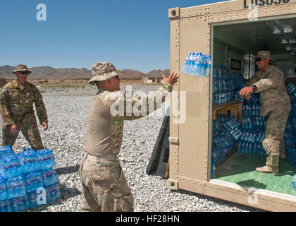 Sgt. Fabricio Granados, an Oakland, Calif., native throws a package of water from a connex to Spc. Daniel Ponce, - Stock Image