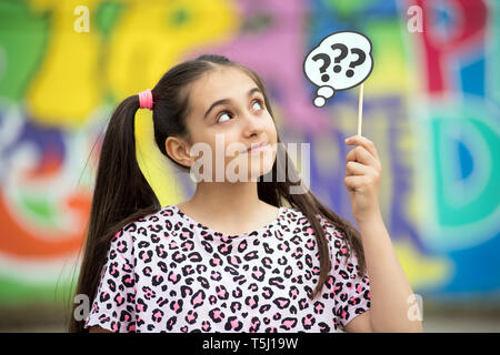 Thoughtful or confused young girl holding up question marks on the end of a stick looking up with a quiet smile - Stock Image