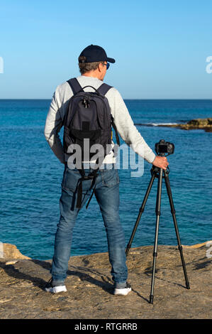 Back view of a photographer wearing a backpack and standing by a camera and tripod looking out to sea. - Stock Image