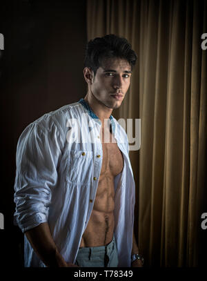Sexy young man dressing by window curtains - Stock Image