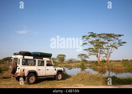 Tanzania, Serengeti. A Land Rover stops by the Seronera hippo pool. - Stock Image