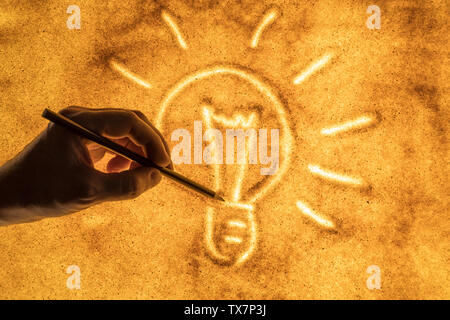 the hands of men draw in the sand a symbol of the bulb. the concept of ideas and inspiration - Stock Image