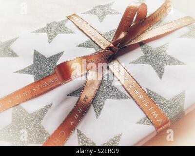 Christmas present decorated with a ribbon tied in a bow - Stock Image