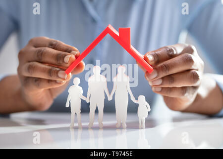 Close-up Of A Person's Hand Protecting Family Figures With Red Roof - Stock Image