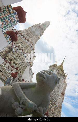Monkey statue with large pagoda in the background in Wat Arun temple in Bangkok, Thailand. - Stock Image
