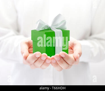 Small green present box in hands - Stock Image