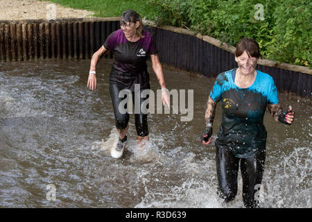 Rather muddy ladies splashing through a water crossing - Stock Image