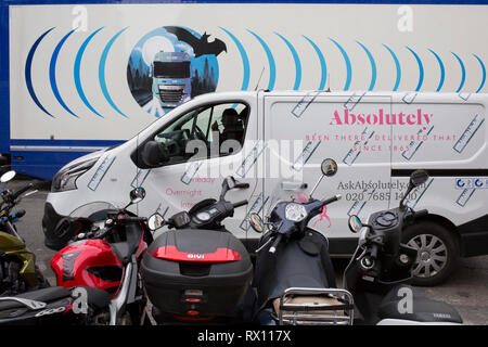 The design on the side of an HGV for the rehearsal studio company 'Fly By Nite' and a courier van of Absolutely, in Great Marlborough Street, on 5th March 2019, in London, England. - Stock Image