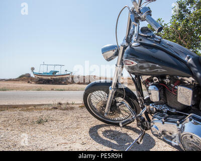 A Harley Davidson motorbike with a fishing boat in the distance on the coast in a hot country - Stock Image