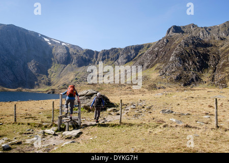 Two hikers in Cwm Idwal with view to Devil's Kitchen in Glyderau mountains of Snowdonia National Park Ogwen North Wales UK - Stock Image