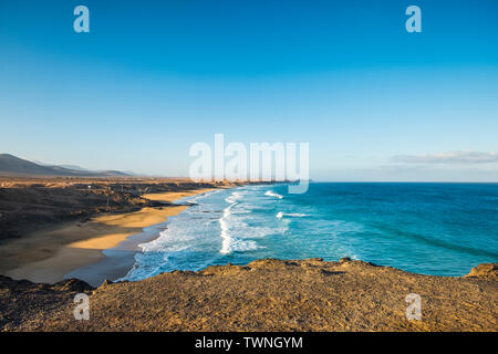 Beautiful wild beach with blue ocean waves and sky - tourism summer vacation scenic place - blue sky and water - cliff point of view and scenery coast - Stock Image