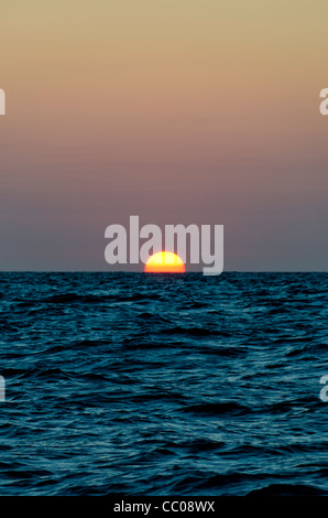 The sun disappears below the horizon over the Coral Sea. The frame is divided evenly between sky and water with - Stock Image